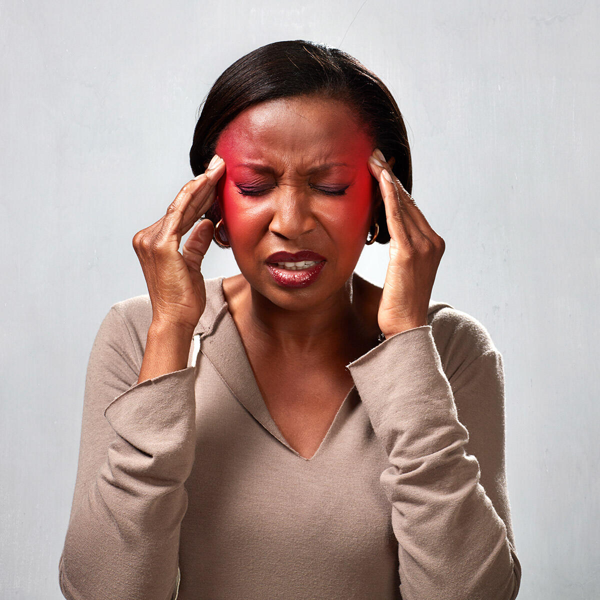 woman with hands to her temples. Red radiates from under her finger tips and she wears a painful expression.