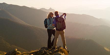 couple hiking on mountain taking a photo