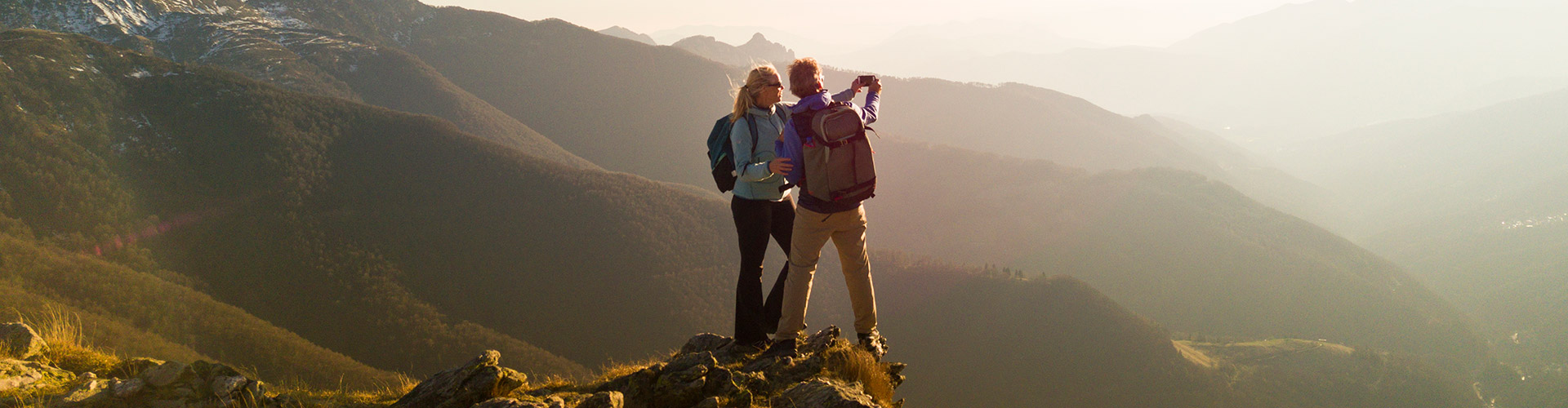couple hiking in the mountains taking a photo