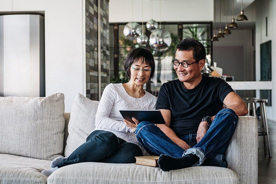 couple on couch looking at tablet