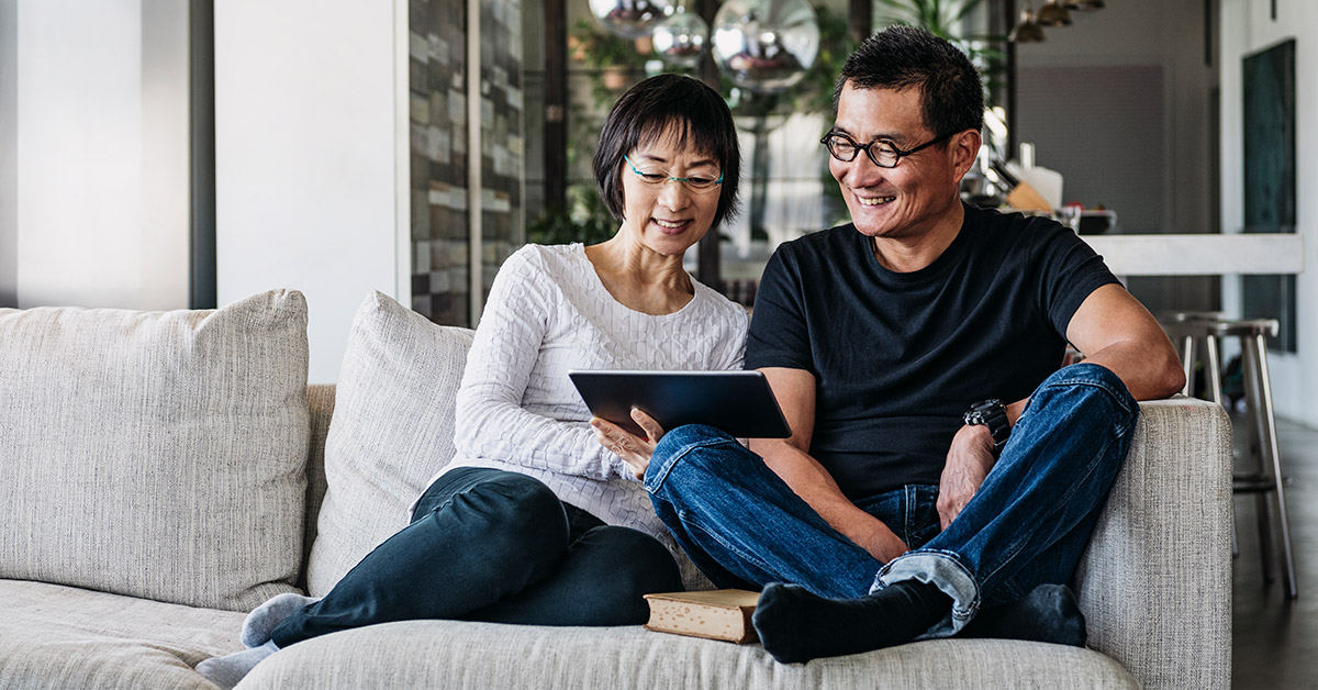 couple on couch looking on ipad