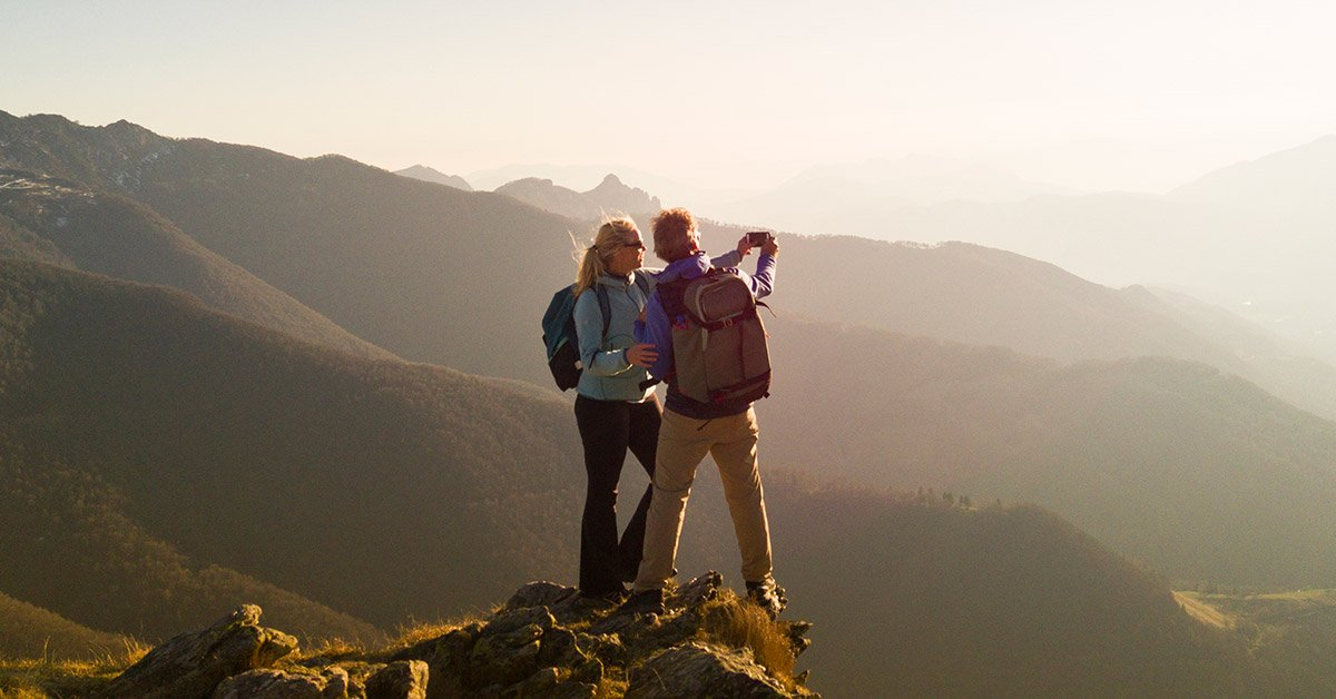 couple hiking on a mountain taking a photo