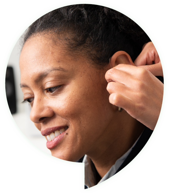 woman getting a hearing aid put in her ear
