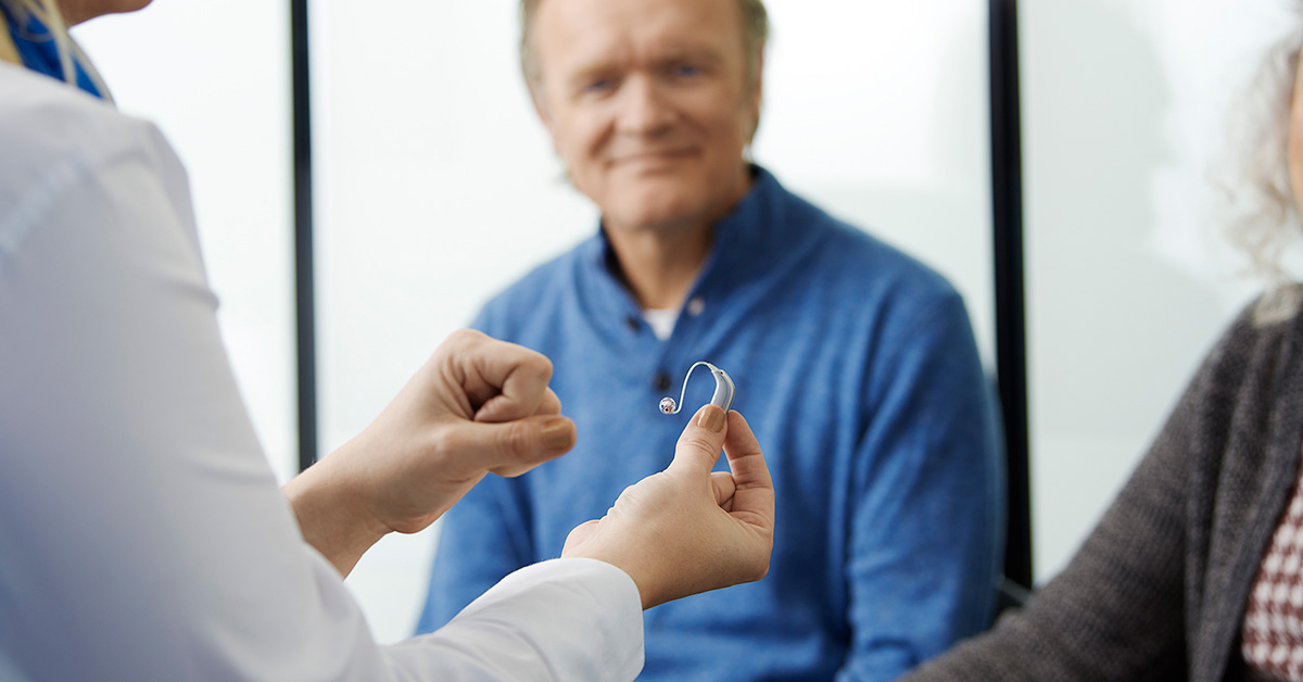 Hearing professional holding hearing aid in front of smiling male client