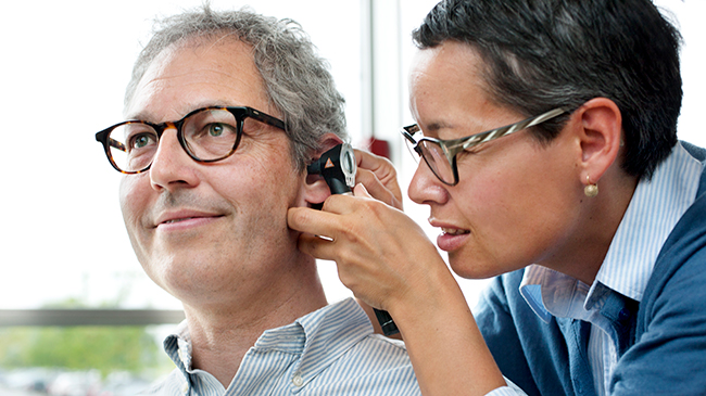 Hearing professional using an otoscope to look inside the ear of a smiling client