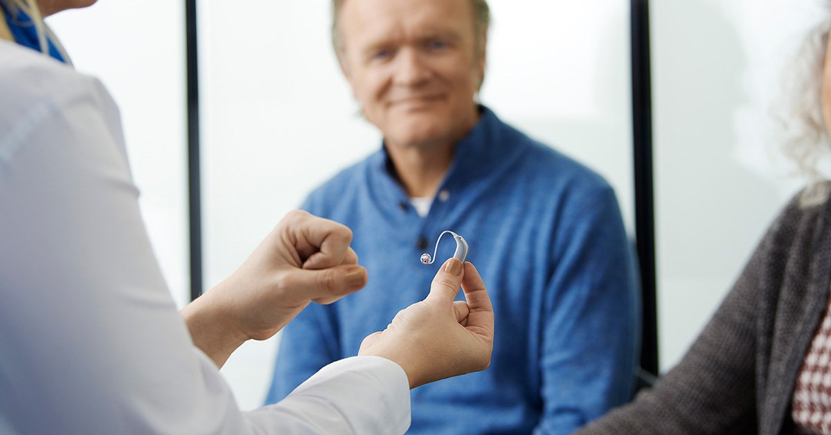 Hearing professional holding hearing aid in front of smiling client