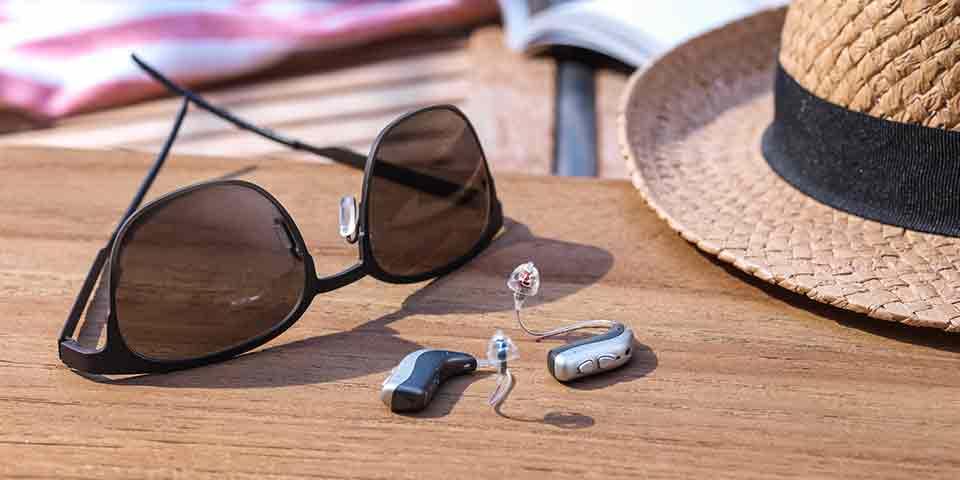 Les nouvelles aides auditives Viron miniRITE T R lithium-ion rechargeables de Bernafon, allongées sur une table à l'extérieur près d'un chapeau et de lunettes de soleil.