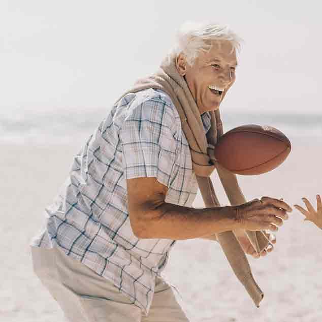 Grand-père à la plage jouant au rugby en famille et profitant de l'instant en utilisant ses aides auditives Viron.