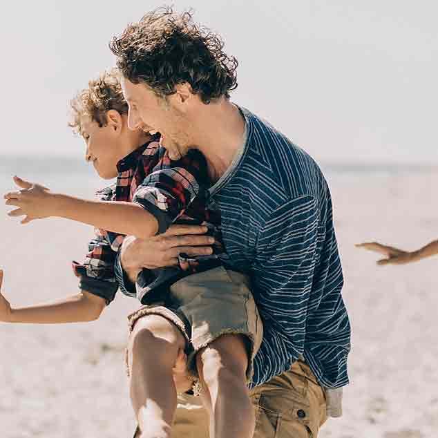 Père à la plage avec la famille tenant le fils et jouant au rugby en profitant du moment.