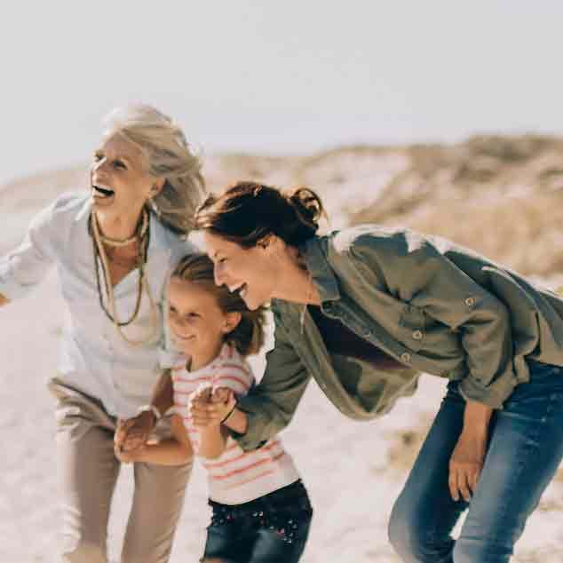Grand-mère, mère et fille jouant avec le reste de la famille à la plage et s'amusant.