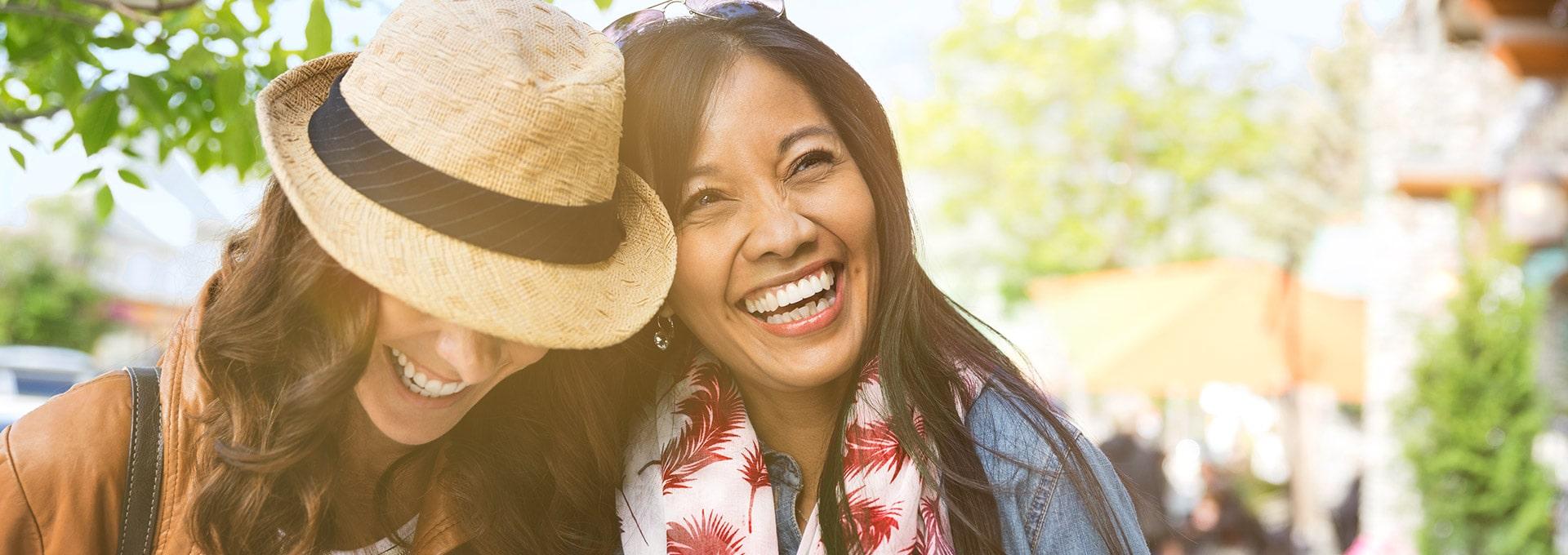 Femmes marchant côte à côté dans la rue et portant un chapeau mais, n'ayant pas de signal de larsen dans leurs aides auditives, grâce au  Dynamic Feedback Canceller.