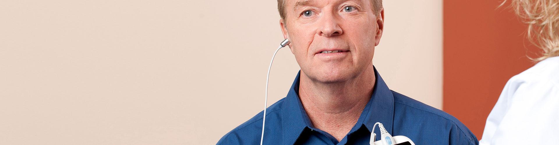 An audiologist testing OAEs on a patient