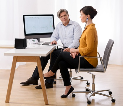Hearing care professional and patient sitting at a desk. The provider is conducting real ear measurements with live speech mapping.