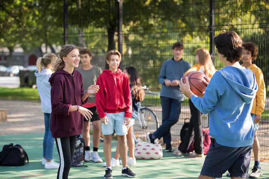 Teen wearing opn play hearing aids playing basketball