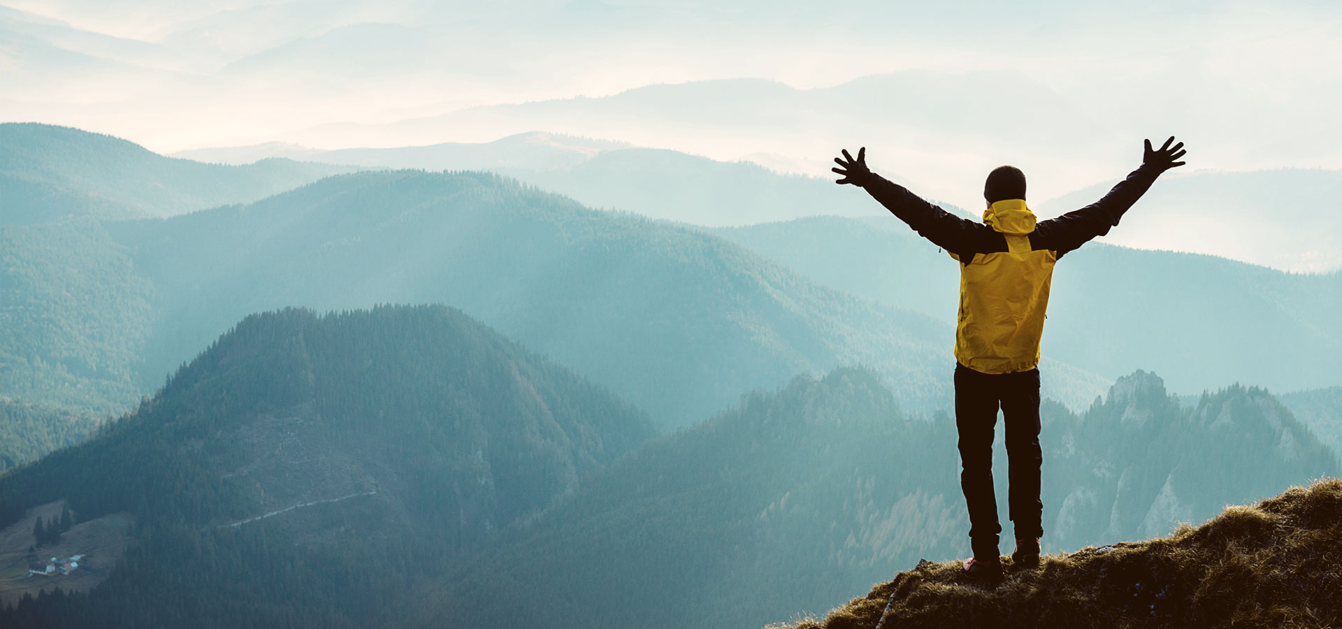 Man with hands in the air on a mountain